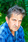 Elderly serious man in summer park — Stock Photo