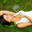 Young girl laying and inflating soap bubbles — Stock Photo