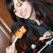 Pretty woman eating sushi with chopsticks in dining room — Stock Photo