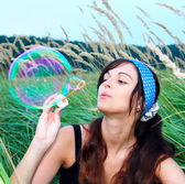 Mladá dívka foukání velké mýdlová bublina — Stock fotografie