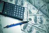 Heap of dollars with pen and calculator — Stock Photo
