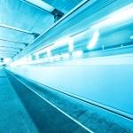Blue underground platform with moving train — Stock Photo #6710629