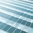 Blue transparent textured wall of glass skyscraper in business c — Stock Photo