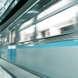 Diminishing blue train leaving the platform — Stock Photo