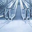 Black moving escalator stairs inside business blue hall - Stock Photo