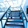 Wooden steps of business luxury staircase in blue office hallway - Stock Photo