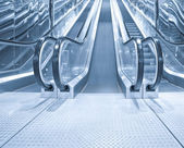 Black moving escalator stairs inside business blue hall — Stock Photo