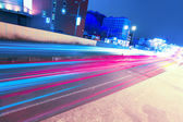 Night traffic through contemporary downtown — Stock Photo