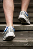 Legs of running man on stairs — Stock Photo