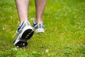 Legs of walking man on grass — Stock Photo
