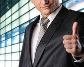 Happy businessman showing his thumb up with smile — Stock Photo