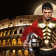 Roman legionary soldier in front of coliseum at night time - Foto Stock