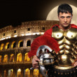 Roman legionary soldier in front of coliseum at night time — Stock Photo