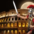 Royalty-Free Stock Photo: Roman legionary soldier in front of coliseum at night time
