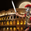 Stock Photo: Romlegionary soldier in front of coliseum at night time