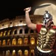 Roman legionary soldier in front of coliseum at night time — Stock Photo #5517984