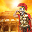 Roman legionary soldier in front of coliseum — Stock Photo #5517986
