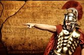 Legionary soldier in front of roman wall — Stock Photo