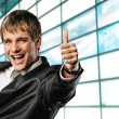 Happy businessman showing his thumb up with smile - Stock Photo