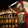 Roman legionary soldier in front of coliseum at night time - Stockfoto