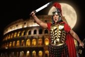 Roman legionary soldier in front of coliseum at night time — ストック写真