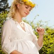 Lovely pregnant woman with a butterfly over blue sky — Stock Photo