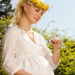 Stock Photo: Lovely pregnant woman with a butterfly over blue sky