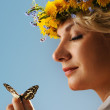 Lovely woman with a butterfly over blue sky — Stock Photo