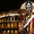 Roman legionary soldier in front of coliseum at night time — Stock Photo #5812178