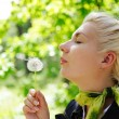Royalty-Free Stock Photo: Close-up portrait of a woman blowing to dandelion flower