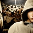 Cool looking hooligan in a graffiti painted gateway — Stock Photo