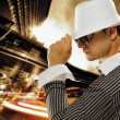 Stylish man in a hat in front of night city — Stok fotoğraf