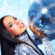 Brunette woman with a disco ball over abstract background — Stock Photo #5867586