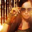 Attractive woman in sunglasses over golden curtains — Stock Photo #5867589