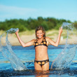 Young happy girl making water splashes — Stock Photo