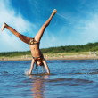 Young girl making cartwheel in the water — Stock Photo #5893261