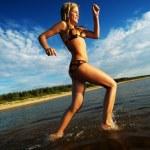 Happy girl running in the sea — Stock Photo