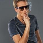 Young stylish man smoking a cigarette — Stock Photo