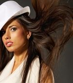 Attractive lady in white hat and blowing hair — Stok fotoğraf