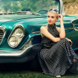 Beautiful lady sitting near retro convertible -  