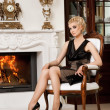 Blond lady near fireplace in a luxury interior - Stock Photo