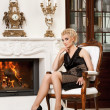 Blond lady near fireplace in a luxury interior — Stock Photo #6229010