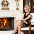 Blond lady near fireplace in a luxury interior — Stock Photo #6229011
