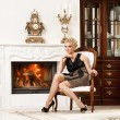 Blond lady near fireplace in a luxury interior — Stock Photo
