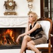 Blond lady near fireplace in a luxury interior — Stock Photo #6229017