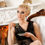 Blond lady drinking coffee in luxury interior — Stock Photo