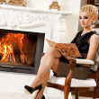 Stock Photo: Blond lady reading book near fireplace