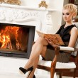Blond lady reading book near fireplace — Stock Photo