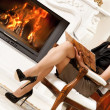 Blond lady reading book near fireplace - Stock Photo
