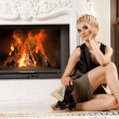 Beautiful blond woman near the fireplace in a luxury interior — Stock Photo #6229031